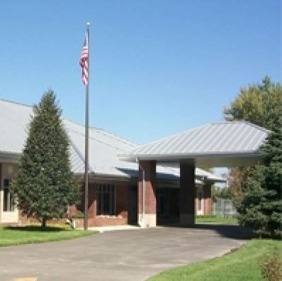 A brick building with a grey roof, with an American flag in front.