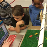 Children gathered around a laptop learning how to do stop motion animation