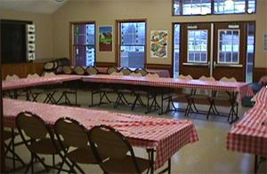A room full of tables with red and white checkered table cloths.