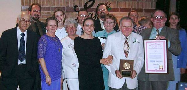 A group of people standing with a man holding a plaque.
