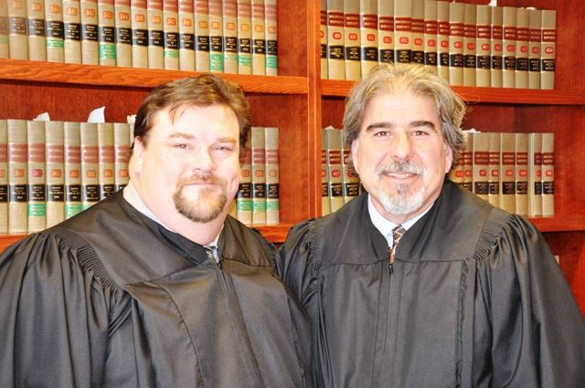 Two men in judge robes standing together.