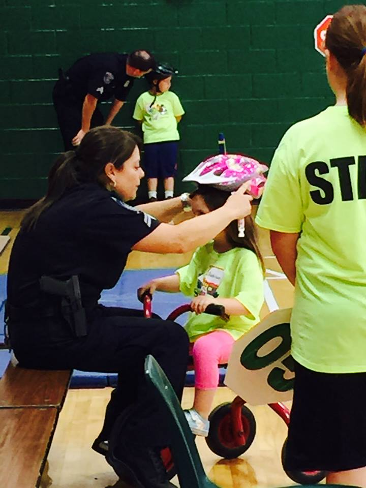 Officer Putting a Helmet on a Young Child Riding a Bike